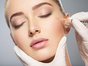 Kobieta podczas zabiegu wygładzania zmarszczek botoksem w okolicach oczu